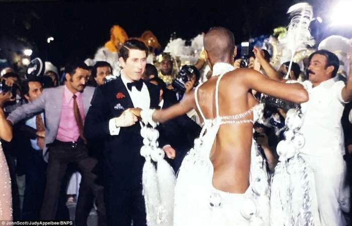 Чарльз в двубортном смокинге с большим галстуком-бабочкой танцует с полуобнажёнными бразильскими красавицами.