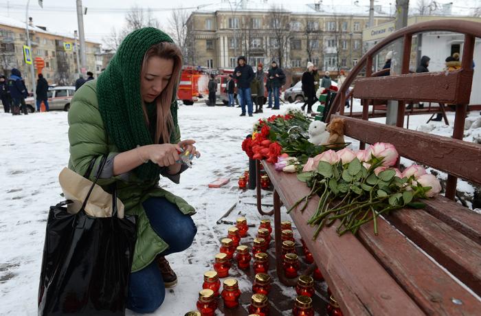 Горожане несут цветы к месте трагедии.