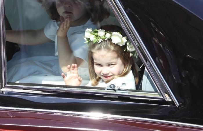 Princesa Charlotte está acenando para a multidão da janela do carro.