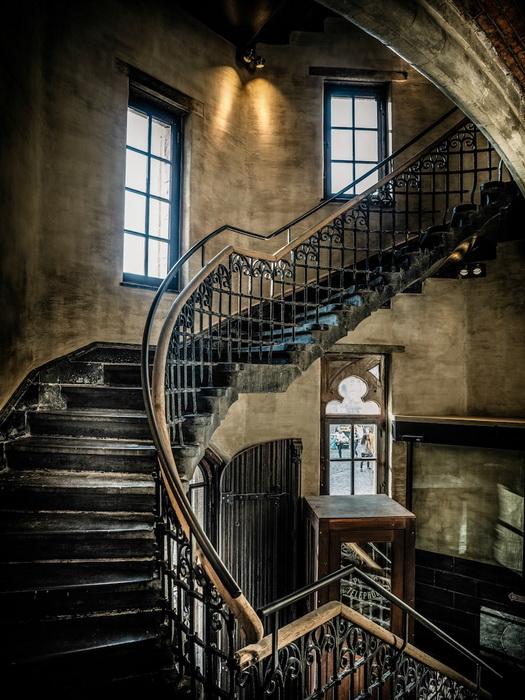 Старинная лестница ведет на этаж, где располагаются комнаты.