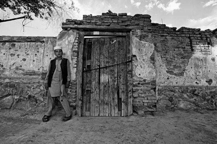 Фотопроект *Лица надежды*. Следы от обстрелов на стенах домов - напоминание о прошлом и предупреждение на будущее