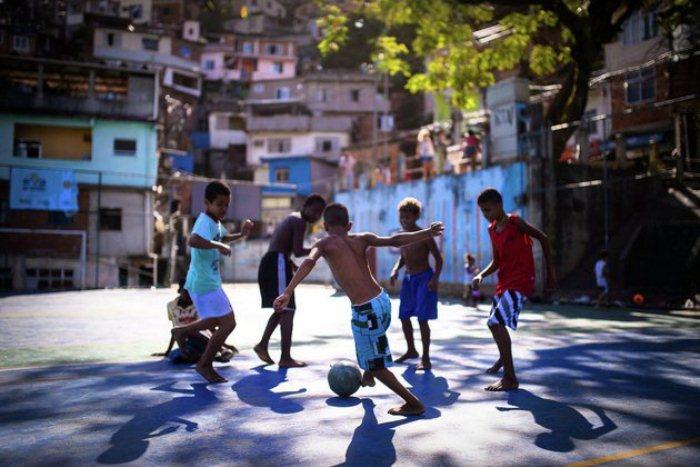 Мальчишки играют в футбол на улице.