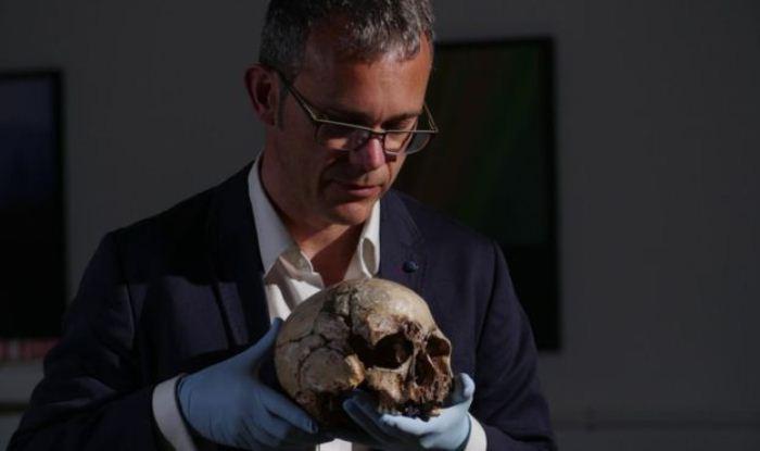 Ученый Ян Барнс держит в руках череп мужчины из Чеддара. Экспонат хранится в природно-историческом музее.