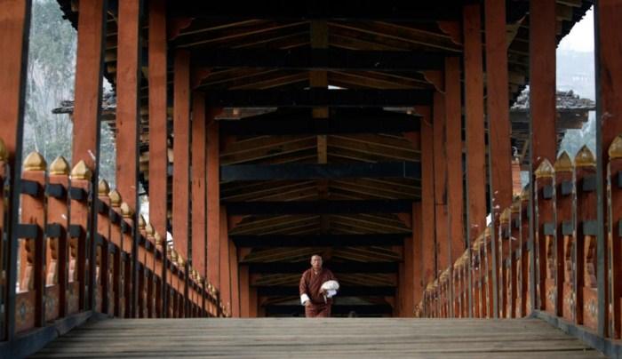 Монах на традиционном деревянном мосту