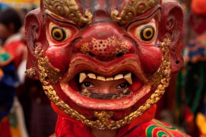 Буддийский монах в маске готовится исполнить танец