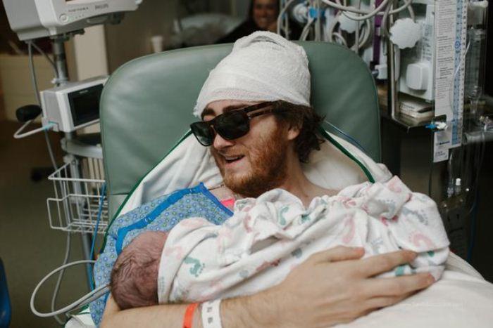 Мужчина, который проходит лечение, держит на руках новорожденного сына.
