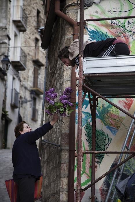 Женщина благодарит художника за его труд букетом сирени.