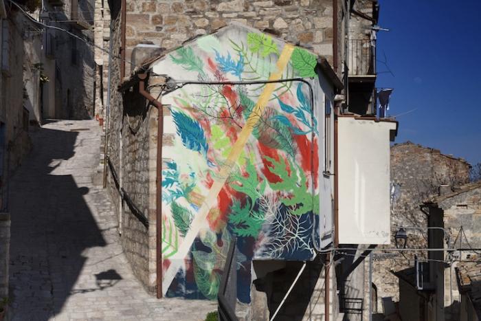 Мурал на стене дома, расположенного на горе. Художник Gola Hundun.