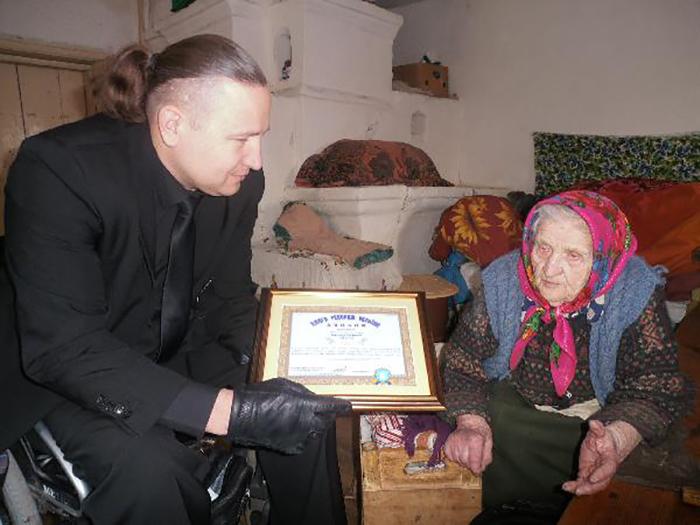 Кристине Нагорной вручают диплом долгожителя.