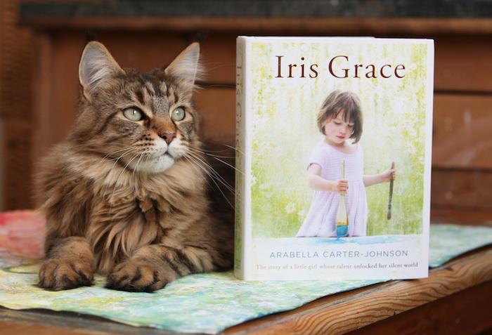 Кот рядом с изданием работ Айрис Грейс