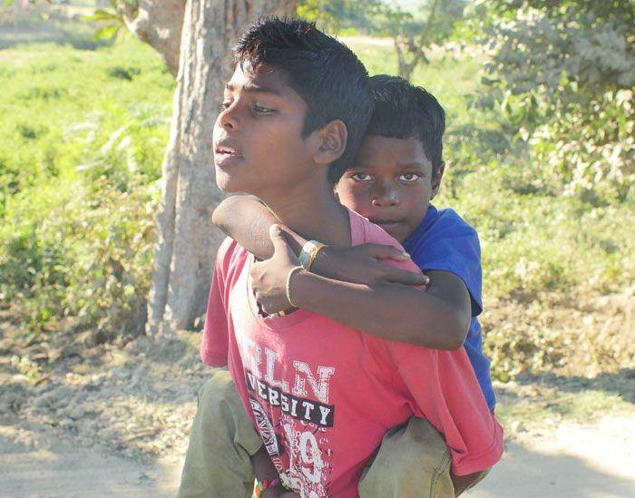 Пострадавший мальчик Акаш, которого брат вынужден носить на руках.