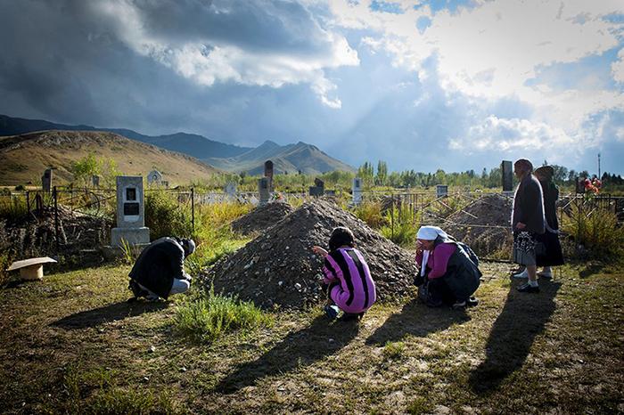 Мать, сестра и возлюбленный у могилы девушки, которая покончила с собой после того, как попала в плен.