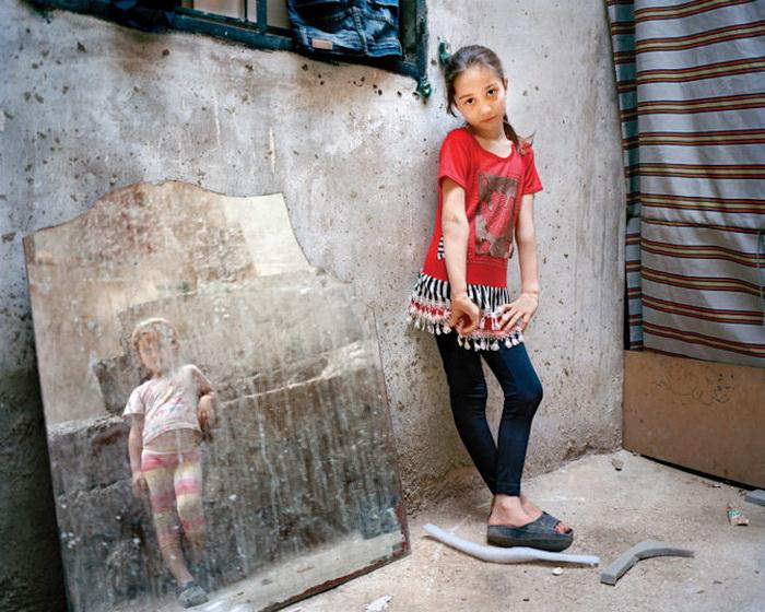 Фотопроект о детях-беженцах в Ливане. Автор: Рания Матар (Rania Matar). Портреты Амал (9 лет) и Зары (5 лет, девочка в зеркале), Бейрут, 2014 год