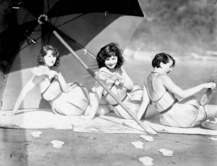 Девушки в деревянных купальниках под зонтом.
