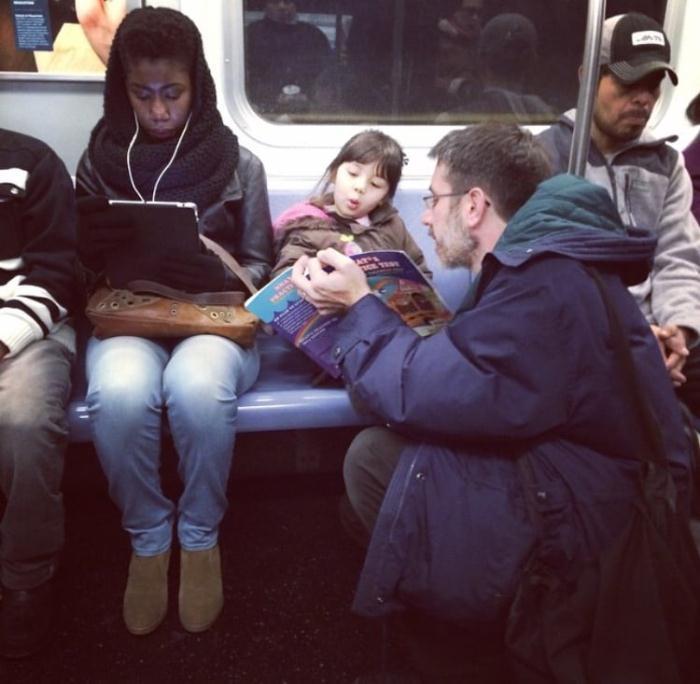 Папа читает дочери книгу в метро.
