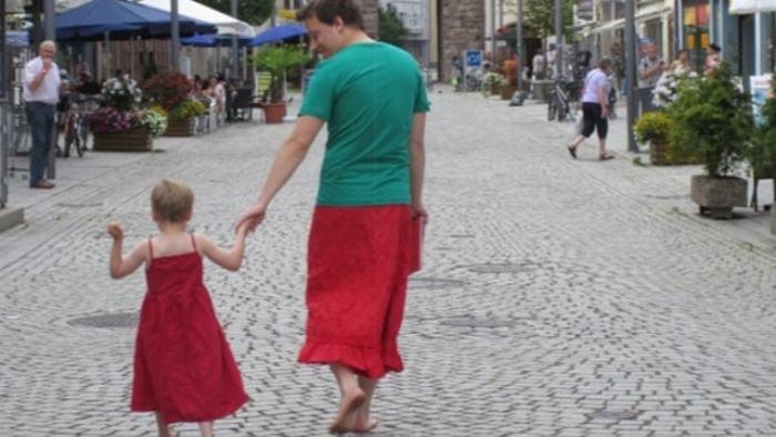 Отец и сын в женских нарядах на улице.