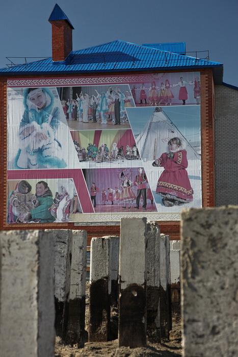 Фотографии людей в национальных костюмах украшают один из домов