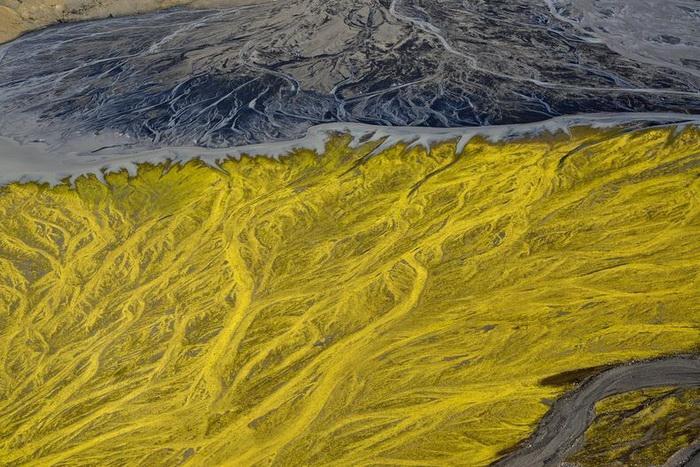 Река, в которую впадает ручей желтого цвета, не смешивающийся с основным потоком