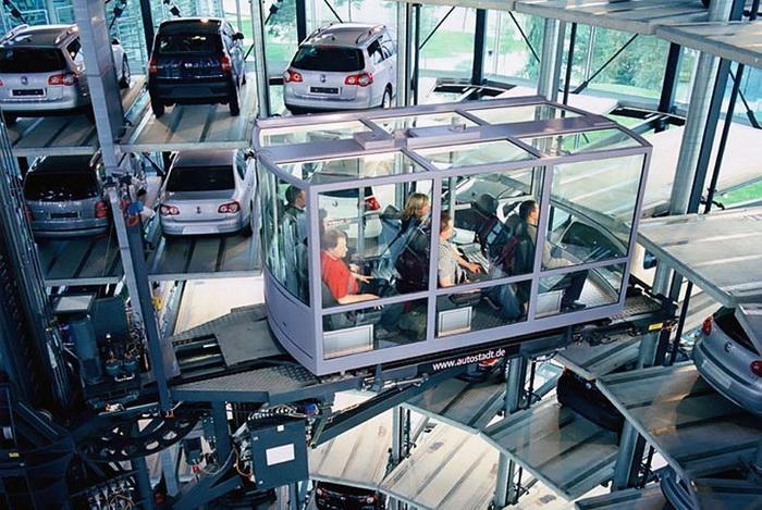 Посетители перемещаются по выставочному центру на стеклянном лифте