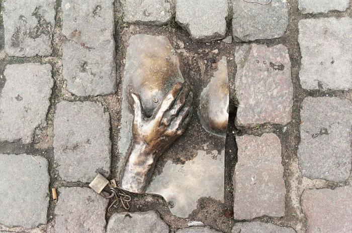 Бронзовый барельеф с изображением обнаженной груди был создан на этой же улице в 1993 году анонимным художником