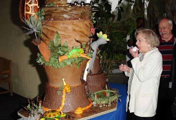 Бетти Уайт пробует кусочек тематического торта, который приготовили к ее дню рождения в зоопарке Лос-Анджелеса.