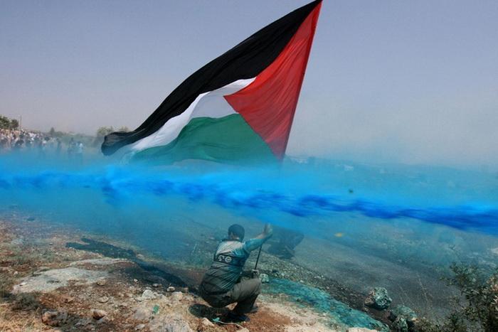 Мужчину с палестинским флагом поливают синей краской, 2006 г.