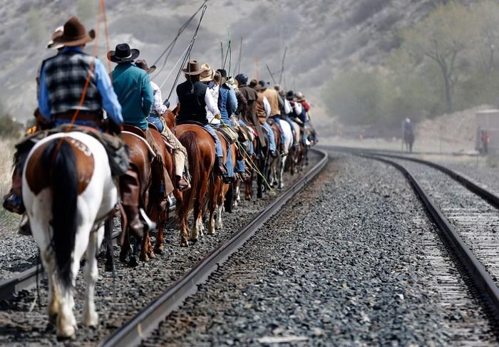 Ковбои едут верхом вдоль железной дороги
