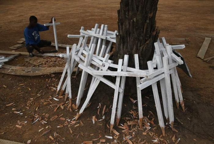 Anthony Johnny изготавливает кресты для новых захоронений. Январь, 2015