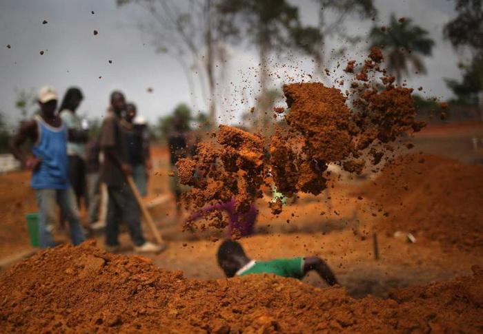 Мужчина роет могилы для традиционного захоронения на специально отведенном кладбище. Январь, 2015