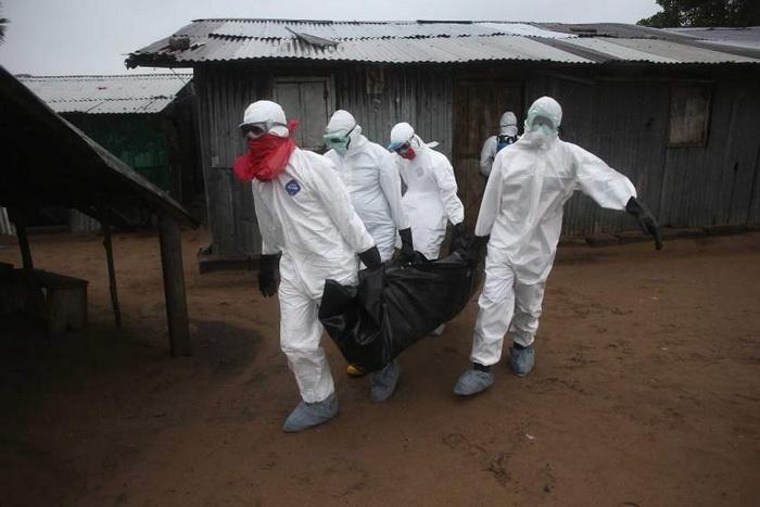 Команда могильщиков выносит тело 60-летнего мужчины, скончавшегося у себя дома. Август, 2014