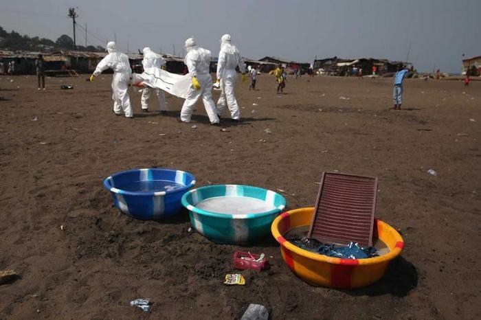 Команда Красного Креста несет тело умершего от болезни для захоронения. Январь, 2015