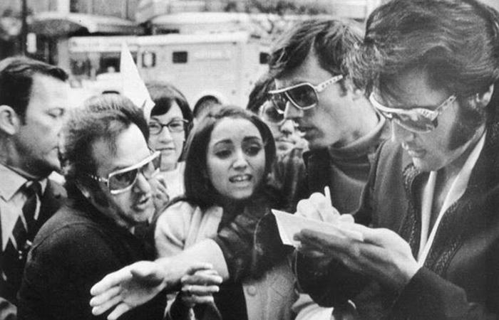 Элвис Пресли раздает автографы поклонникам перед концертом в Детройте.