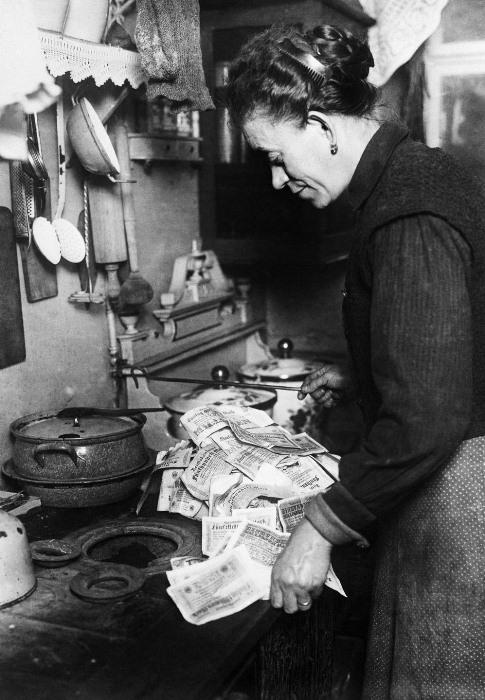 Хозяйка планирует разжечь огонь, используя банкноты.