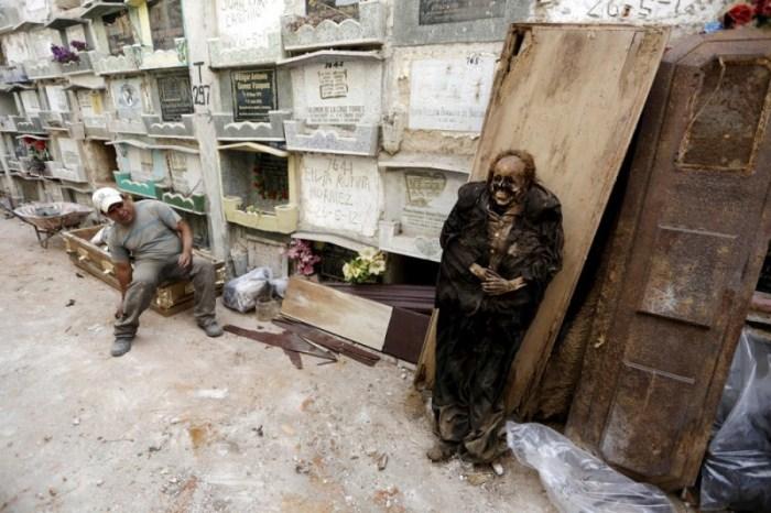 Чистильщик могил сидит на крышке гроба рядом с мумией