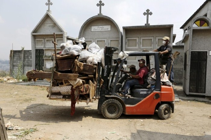 Чистильщики могил отвозят останки к братской могиле