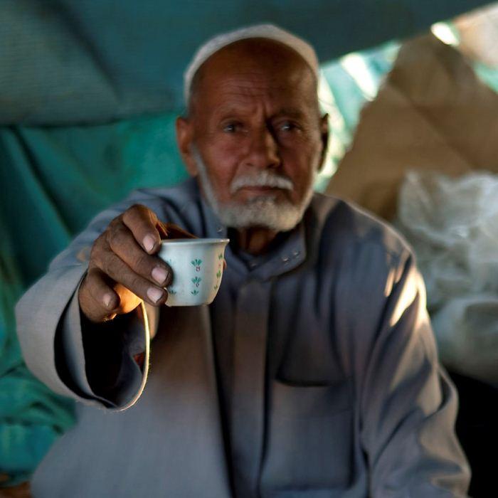 Мужчина протягивает фотографу чашку чая.