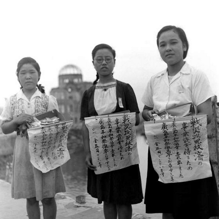 Девушки продают ленты мира на празднике