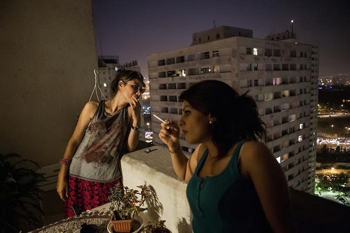 Женщины с непокрытой головой курят и отдыхают на балконе
