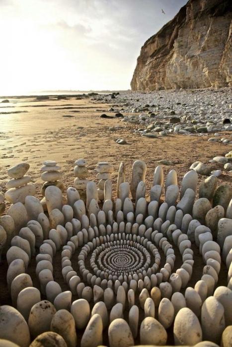 Ленд-арт из белоснежных камней на пляже.