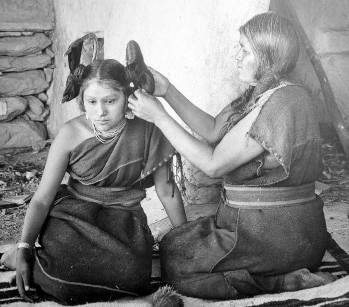 Мать делает прическу дочери.