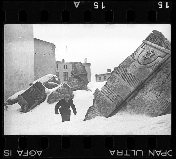 Мужчина идет среди руин синагоги.