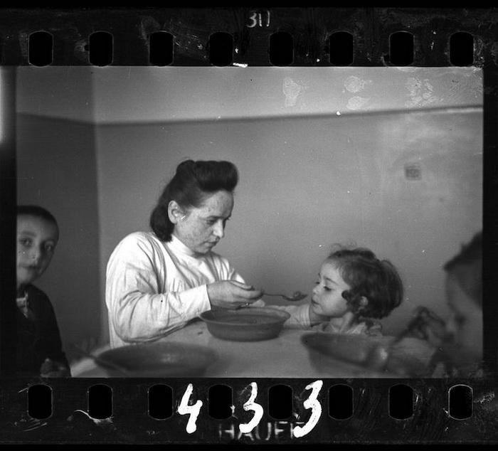 Женщина кормит ребенка в сиротском доме.