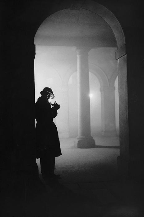 Мужчина курит трубку в тумане, стоя под аркой, 23 декабря 1935 года