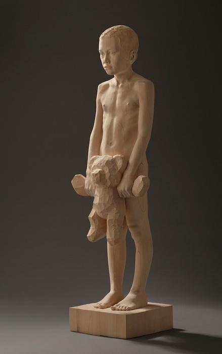 Деревянная скульптура, изображающего мальчика с плюшевым медведем