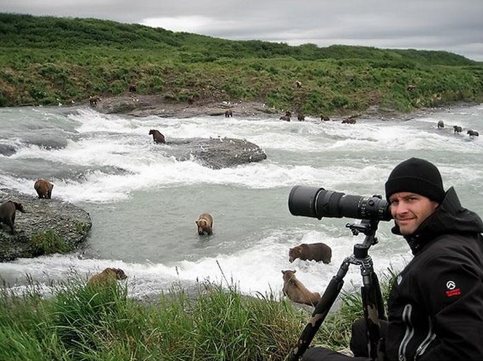 Фотограф Марсель Ван Остен на фоне медведей, охотящихся за лососем