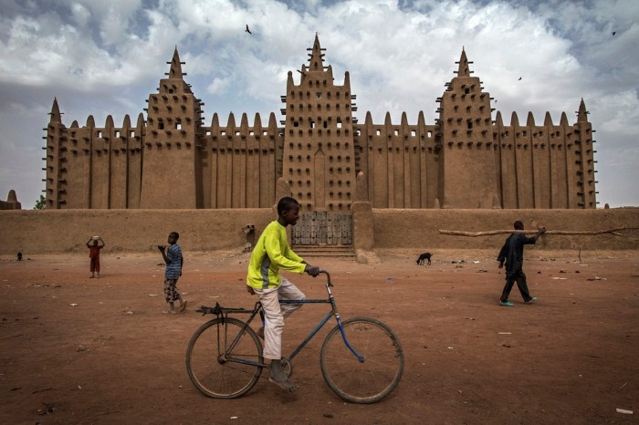 Парень на велосипеде на фоне Великой мечети Дженне.