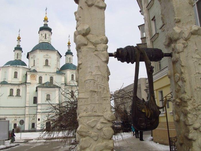 Памятник-фонтан в виде сумки с монетами.
