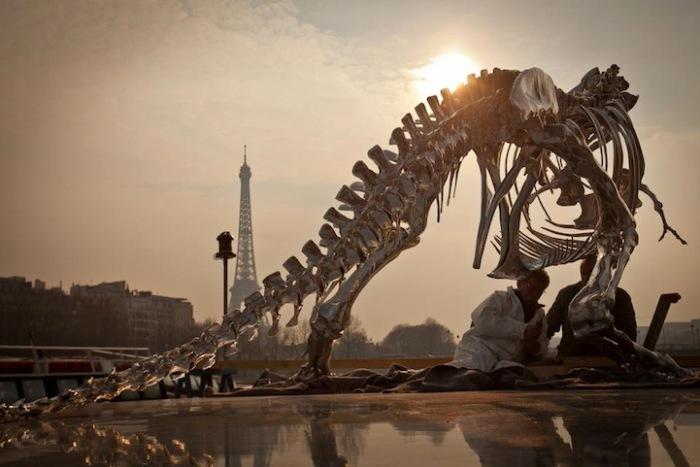 Хищник-тираннозавр угрожающе смотрит на Эйфелеву башню