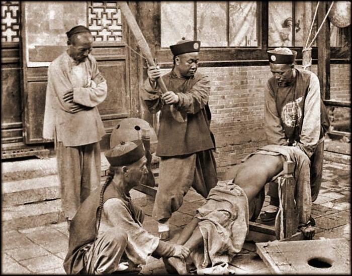 Публичные наказания. В коммунистическом Китае порка преступников осуждалась, как пример жестокости империи Цин. Неизвестное месторасположение, 1900 г.