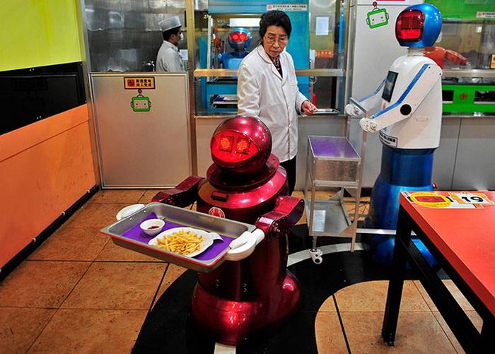 Несколько людей координируют работу роботов в ресторане